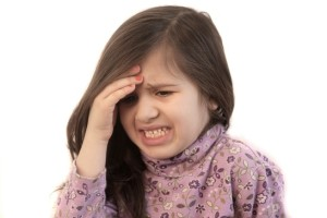 Bambina si tiene la fronte per il mal di testa