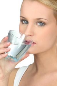 Donna beve bicchiere d'acqua come rimedio per l'otite media