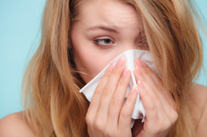 Donna che soffre di allergia agli acari si soffia il naso
