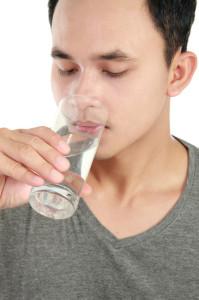 Uomo beve un bicchiere di acqua a piccoli sorsi per contrastare le coliche addominali