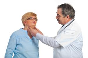 Medico esamina il gozzo tiroideo ad una paziente di sesso femminile con età superiore ai 50 anni