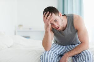 Uomo seduto sul letto con stanchezza persistente da ipotiroidismo