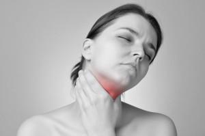 Donna con la mano sul collo affetta da tiroidite