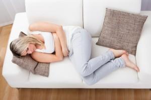 Donna sdraiata sul divano con dolori allo stomaco