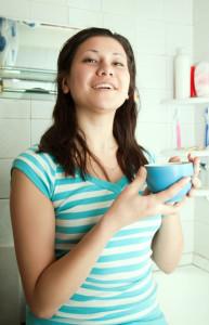 Donna con bicchiere tra le mani per gli sciacqui di bicarbonato
