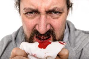 Uomo tampona le gengive sanguinanti con un fazzoletto