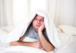 Uomo sotto le coperte con problemi di insonnia