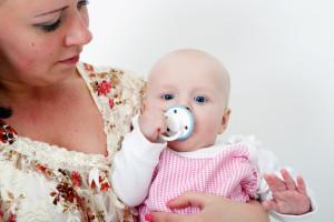 Neonato con il ciuccio in braccio alla mamma
