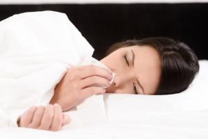 Donna a letto che soffre di rinite allergica