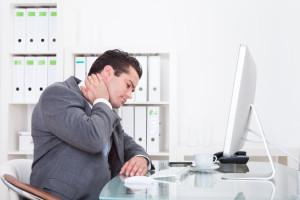 Uomo seduto al computer con dolore al collo