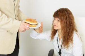 Giovane donna rifiuta un piatto con amburger