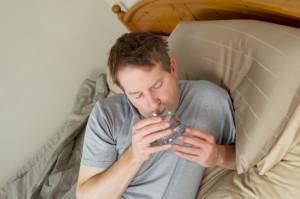 Umo a letto mentre beve un bicchiere di acqua