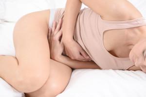 Donna sdraiata a letto con forti dolori addominali