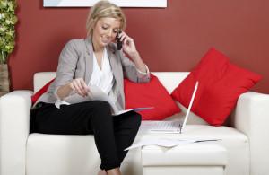 Donna lavora sul divano di casa